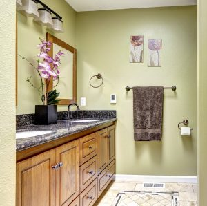 Cozy bathroom interior in ivory tones with dark granite counter top tile flooring and orchid pot on the cabinet