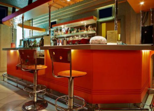 Bar counter and barstools  in empty cafe-bar with orange interior