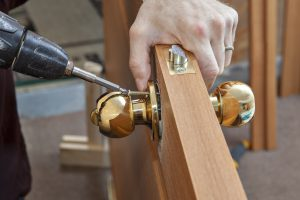 Install the door handle with a lock Carpenter tighten the screw using an electric drill screwdriver close-up.