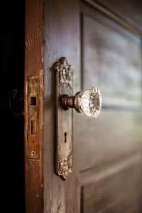 An old door open with an ornate door knob.
