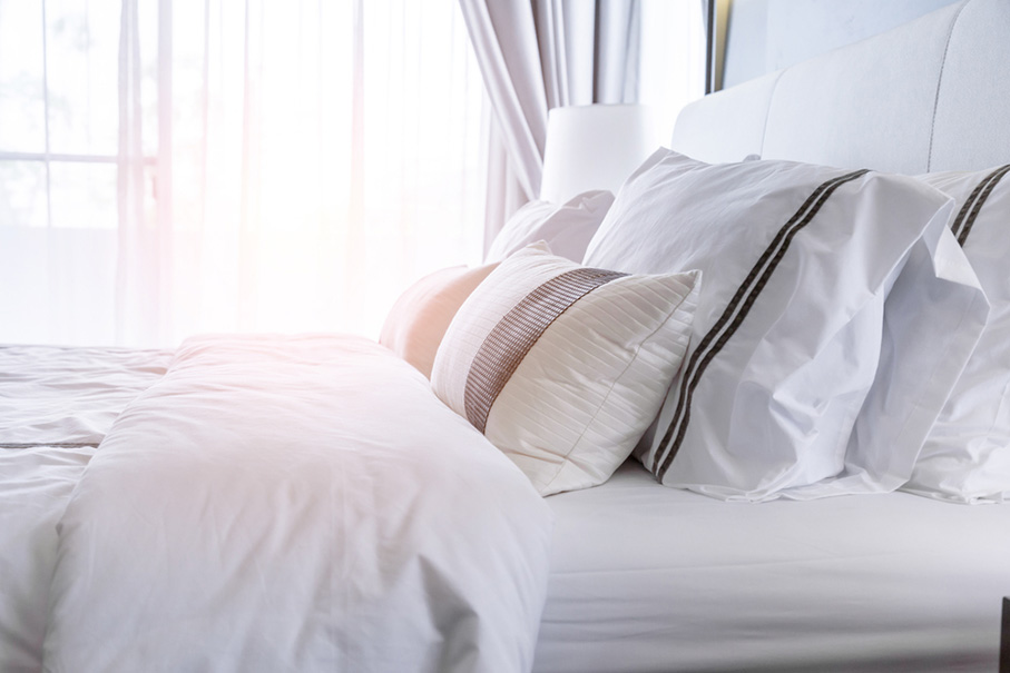 Bed with clean white pillows and bed sheets