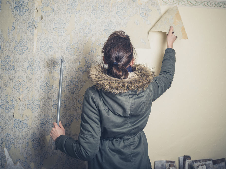 woman wearing a warm winter coat stripping wallpaper