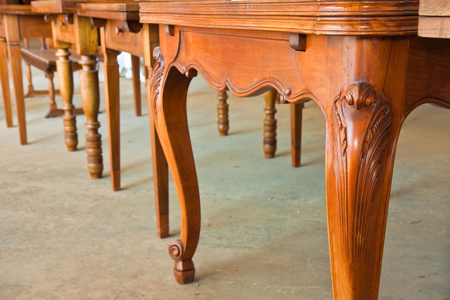 a close up of several old wooden tables in a line