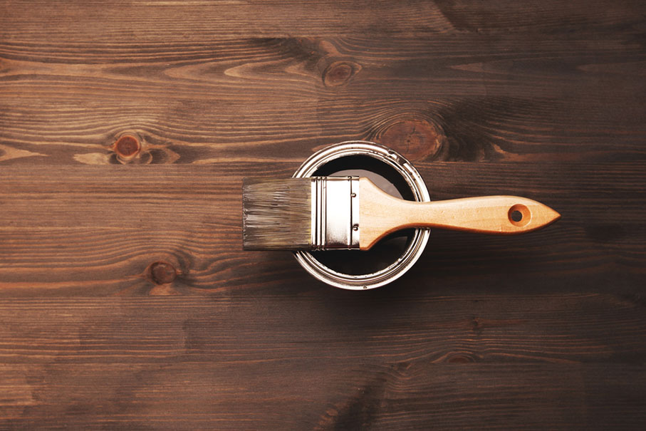 a paintbrush sitting on top of a newly opened can of grey paint
