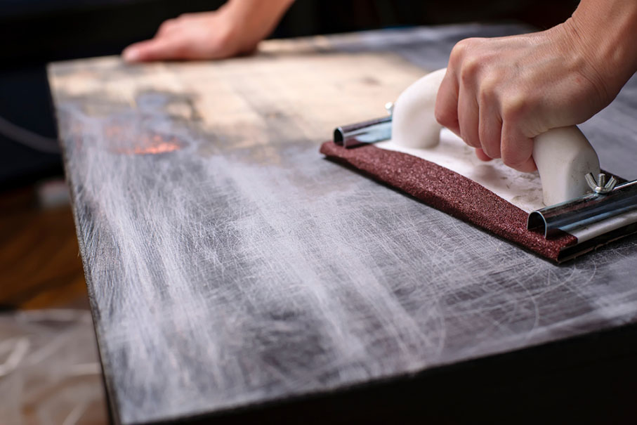 a person prepping a wooden table surface for refinishing